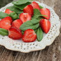 Fresh spinach salad with strawberries on a wooden background Royalty Free Stock Image