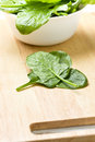 Fresh spinach with water drops on a cutting board Royalty Free Stock Photo