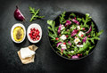 Fresh spring salad with rucola feta cheese and red onion pomegranate seeds in black bowl on chalkboard background Stock Image