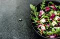 Fresh spring salad with rucola feta cheese and red onion pomegranate seeds in black bowl on chalkboard background Royalty Free Stock Image