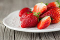 Fresh strawberries juicy in a white bowl on a wooden background selective focus Stock Image
