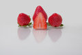 Fresh strawberries a nice display of with reflections showing a sliced half Royalty Free Stock Photo