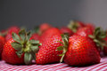 Fresh strawberries sitting on red gingham tablecloth Royalty Free Stock Images