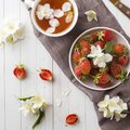 Fresh strawberries and tea with Jasmine flowers on a light background. Summer concept Royalty Free Stock Photo