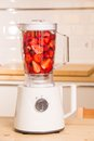 Fresh strawberries in white blender on a wooden table kitchen Stock Photography