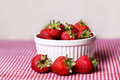 Fresh strawberries in white bowl on red gingham tablecloth Royalty Free Stock Image