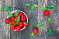 Fresh strawberries in white vintage bowl on old wooden table. Green mint leaves and ripe berries from garden on background Royalty Free Stock Photo