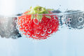 Fresh strawberry in bubbles close up macro of a bright red floating sparkling water and covered oxygen blackberry and Stock Photo
