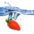Fresh strawberry dropped into blue water Royalty Free Stock Photo