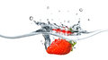 Fresh strawberry dropped into blue water with splash Royalty Free Stock Photo