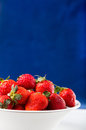 Fresh strawberry in plate on blue background Royalty Free Stock Photo