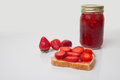 Fresh strawberry preserves a nice display of in a glass mason jar with spread on a slice of bread along with sliced Royalty Free Stock Photos
