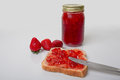 Fresh strawberry preserves a nice display of in a glass mason jar with spread on a slice of bread with knife as well a Stock Images