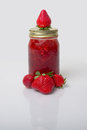 Fresh strawberry preserves a nice display of in a glass mason jar and with strawberries Royalty Free Stock Photography