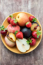 Fresh summer fruits in plate over wooden background Royalty Free Stock Photography
