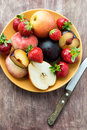 Fresh summer fruits in plate over wooden background with knife selective focus Stock Images
