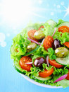 Fresh summer salad leafy green with tomato and olives under a hot sun with flare andd bokeh Royalty Free Stock Photos