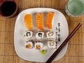 Fresh sushi and sashimi on a plate with a cup of sake chopsticks Royalty Free Stock Photography