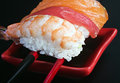 Fresh sushi served in a red plate with black stripes focus on the first prawn Stock Photos