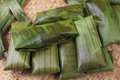 Fresh tamales pile of freshly wrapped in banana leaves on palm woven mat prior to cooking Stock Image