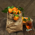 Fresh tangerines in recycle paper bag and glass of juice on wood wooden table closeup Royalty Free Stock Photo