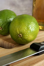 Fresh tangy green limes persian on a chopping board waiting to be sliced for drinks or cooking Royalty Free Stock Images