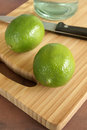 Fresh tangy green limes persian on a chopping board waiting to be sliced for drinks or cooking Stock Photos