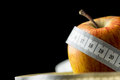Fresh tasty apple wrapped with a measuring tape close up of natural source of vitamins and minerals white copy space on Royalty Free Stock Photos