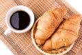 Fresh and tasty french croissants in a basket and cup of coffee served on white background Royalty Free Stock Photo