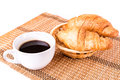 Fresh and tasty french croissants in a basket and cup of coffee served on white background Royalty Free Stock Image