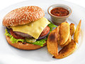 Fresh tasty hamburger with fried potatoes and salsa dip on a round plate Royalty Free Stock Photo
