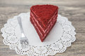 Fresh tasty sweet piece of red velvet cake on a white napkin and a dessert fork on a wooden background Royalty Free Stock Photo