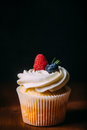 Fresh tasty vanilla cupcakes with berries. Selective focus. Dark wooden background.Rustic style, place for text Royalty Free Stock Photo