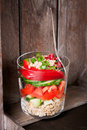 Fresh tasty vegetarian or vegan layer salad with tomatoes, cucumber, paprika, green onion and grain in a glass on a wooden backgro Royalty Free Stock Photo
