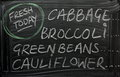 Fresh today green vegetables cabbage broccoli beans and cauliflower advertised on a used blackboard provide a daily source Royalty Free Stock Photography