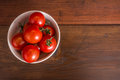 Fresh tomato in bowl on wooden table Royalty Free Stock Photo