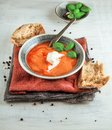 Fresh Tomato soup in a bowl with tomatoes and basil on a white kitchen table Royalty Free Stock Photo