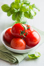 Fresh tomatoes and basil on kitchen table Royalty Free Stock Photo