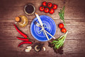 Fresh tomatoes, chili pepper and other spices and herbs around modern blue plate in the center of wooden table. Top view. Royalty Free Stock Photo