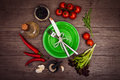 Fresh tomatoes, chili pepper and other spices and herbs around modern green plate in the center of wooden table. Top view. Fork an Royalty Free Stock Photo