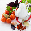 Fresh tomatoes herbs spices and oil jug on light background selective focus Stock Image