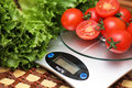 Fresh tomatoes on kitchen scales weighing Royalty Free Stock Photo