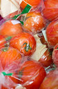 Fresh tomatoes packed in transparent plastic bag close up of the market Stock Photo