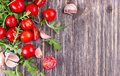 Fresh tomatoes with salad leaves on the table. Background.