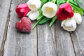 Fresh tulips with a red heart on wooden background Royalty Free Stock Photography