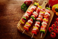 Fresh uncooked meat kebabs ready for grilling with colorful red green and yellow sweet pepper onion and tomato arranged on a Royalty Free Stock Photos