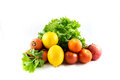 Fresh vagetable a group of vegetable that are a green lettuce two lemons three tomatoes and an apple Stock Photo