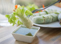 Fresh vegetable noodle spring roll on fork with spicy sauce Royalty Free Stock Photo