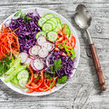 Fresh vegetable salad with red cabbage, cucumber, radish, carrots, sweet peppers, red onion and parsley on a white plate. Royalty Free Stock Photo