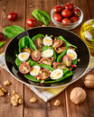 Fresh vegetable salad with spinach, cherry tomatoes, quail eggs, pomegranate seeds and walnuts in black plate on wooden table. Royalty Free Stock Photo